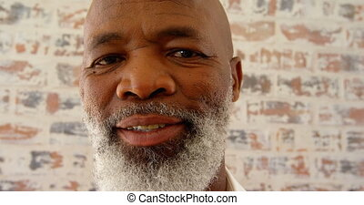 Front view of mature black man looking at camera in a comfortable home 4k