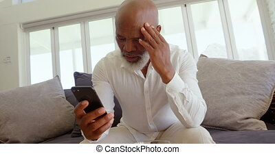 Front view of mature black man sitting on the couch and using mobile phone in a comfortable home 4k