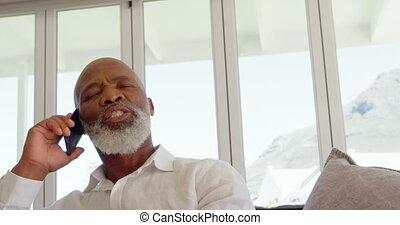 Front view of mature black man talking on mobile phone in a comfortable home 4k