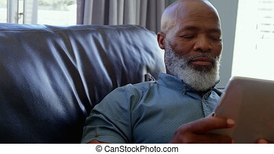 Front view of mature black man using digital tablet in a comfortable home 4k