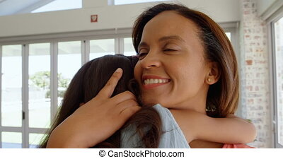 Front view of mature black mother embracing her daughter in living room of comfortable home 4k