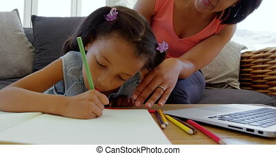 Front view of mature black mother helping her daughter with homework in a comfortable home 4k