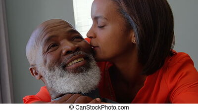 Front view of mature black woman kissing on mans cheek in a comfortable home 4k
