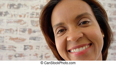 Front view of mature black woman looking at camera in a comfortable home 4k