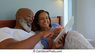 Front view of mature Caucasian couple using digital tablet on bed in a comfortable home 4k