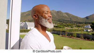 Front view of mature Caucasian man having coffee in balcony ...