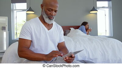 Front view of mature Caucasian man using digital tablet in bedroom at a comfortable home 4k