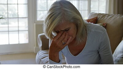 Front view of mature caucasian woman crying while sitting on...
