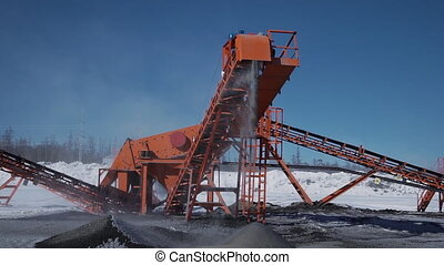 Front view of mechanism with falling stones at construction site of oil refinery outdoors.