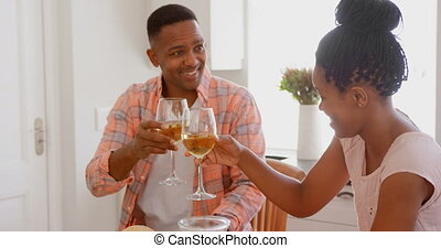 Front view of mid adult black couple toasting wine glasses at dining table in a comfortable home 4k