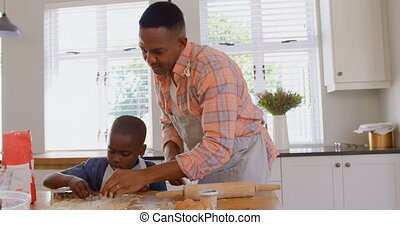 Front view of mid adult black father and son baking cookies in kitchen of comfortable home 4k
