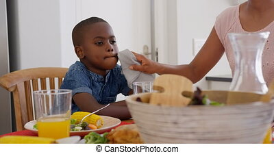 Front view of mid adult black father wiping sons mouth at dining table in a comfortable home 4k