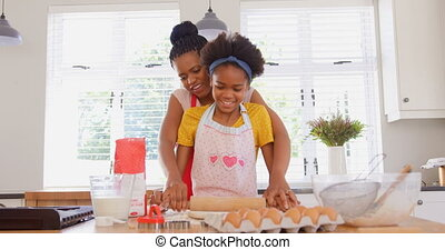 Front view of mid adult black mother and daughter rolling dough in kitchen of comfortable home 4k