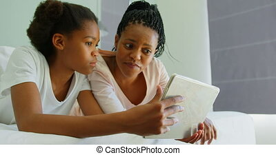 Front view of mid adult black mother and daughter using digital tablet on bed in comfortable home 4k