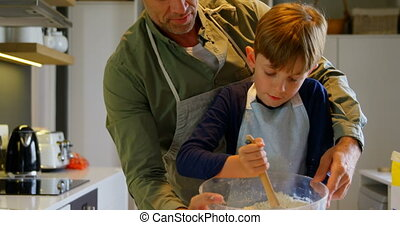 Front view of mid adult Caucasian father and son baking ...
