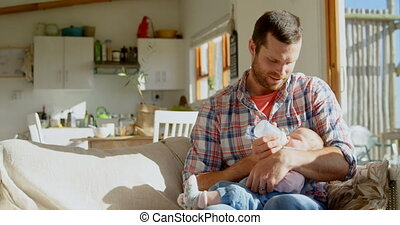 Front view of mid adult caucasian father feeding milk his ...