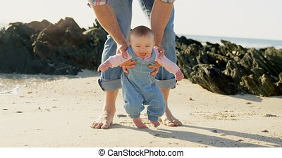 Front view of mid adult caucasian father helping baby to ...