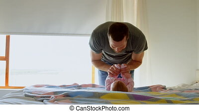 Front view of mid adult caucasian father playing with baby on bed in a comfortable home 4k