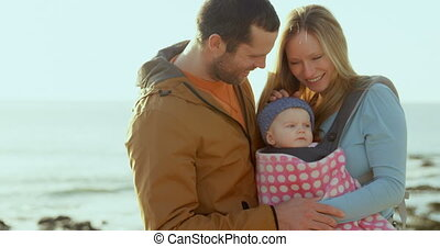 Front view of mid adult caucasian parents looking at baby at...