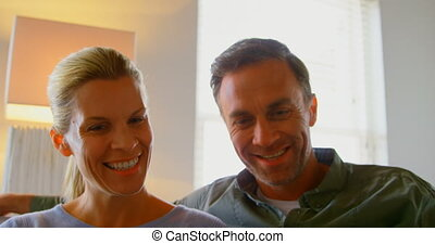 Front view of middle aged Caucasian couple using digital tablet on sofa in a comfortable home 4k