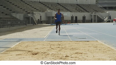 Front view of a mixed race male athlete practicing at a sports stadium, doing long jump, slow motion. Track and Field Sports Training in Stadium.