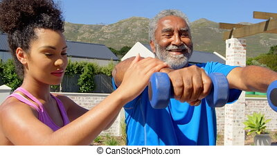 Front view of mixed-race personal trainer exercising with ...
