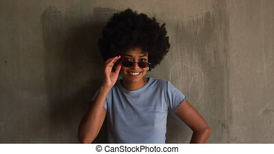 Front view of happy mixed race woman enjoying free time in an urban park on a sunny day, in sunglasses standing by a wall smiling to camera, slow motion