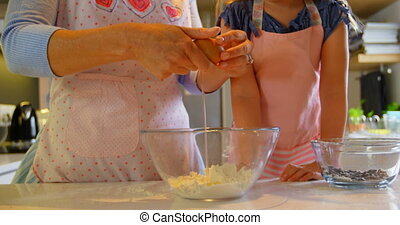 Front view of mother and daughter baking cookies in kitchen of comfortable home 4k