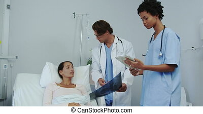 Front view of multi-ethnic male and female doctor showing medical report to patient in ward 4k