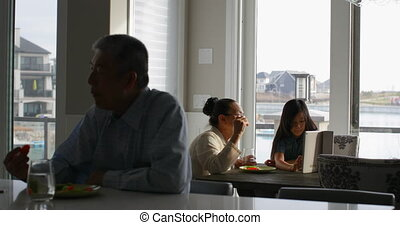 Front view of multi-generation asian family eating food at dining table in a comfortable home 4k