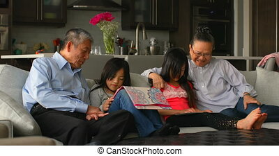 Front view of multi-generation asian family using digital tablet in a comfortable home 4k
