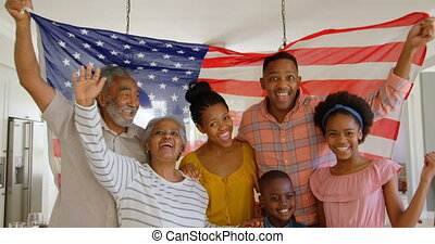 Front view of multi-generation black family holding american flag in a comfortable home 4k