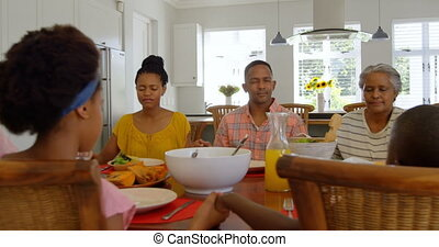 Front view of multi generation black family praying together at dining table in comfortable home 4k