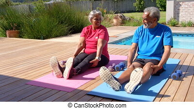 Front view of old asian senior couple exercising in the backyard of their home 4k