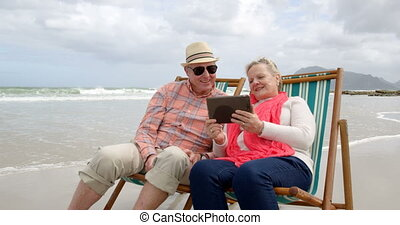 Front view of old caucasian senior couple using digital tablet and sitting on sunlounger a beach 4k