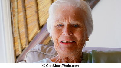 Front view of old Caucasian senior woman looking at camera in a comfortable home 4k