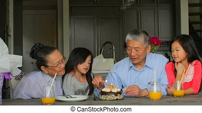 Front view of old senior asian grandfather lightning birthday cake candles in a comfortable home 4k