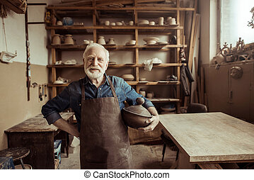 Front view of proud senior potter in apron standing with ceramic bowl at workshop