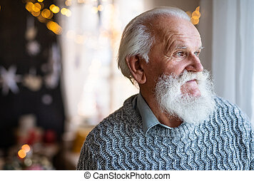 Front view of sad and lonely senior man indoors at home at Christmas.