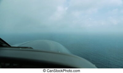 Wide still shot from an aircraft's cockpit of calm blue sea water as it gets lower, heading towards its landing Island, Great Barrier Reef.