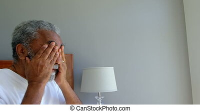 Front view of senior black man sitting on bed and rubbing his eyes in a comfortable home 4k