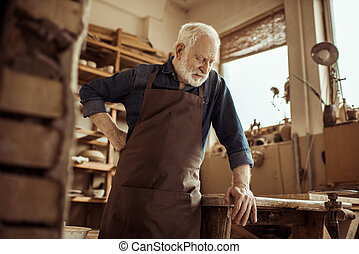Front view of senior potter in apron standing and leaning on table against shelves with pottery goods at workshop