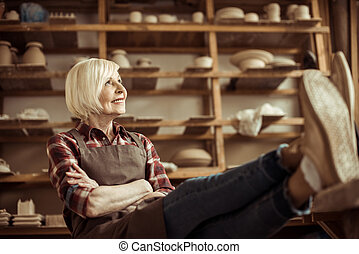 Front view of senior woman sitting on chair with legs on table against shelves with pottery goods