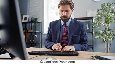 Front view of serious man in suit working on computer