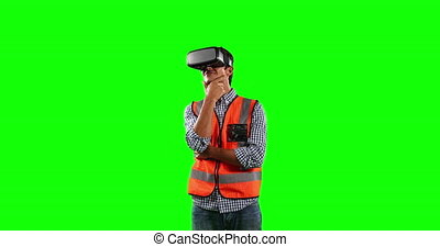 Front view of site worker using virtual reality with green ...