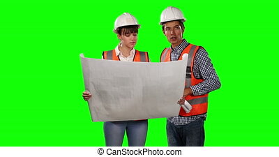Front view of site workers looking at site map with green screen