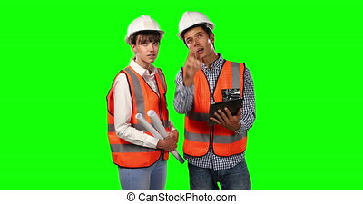 Front view of site workers using digital tablet with green screen