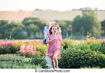 Front view of small girl running in the backyard garden.