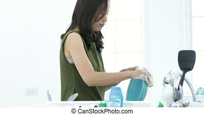 Front view of smiling Asian girl washing dishes and thinking