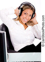 front view of smiling businesswoman listening music